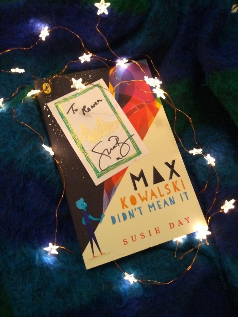 The book Max Kowalski Didn't Mean It by Susie Day, surrounded by star-shaped lights on a dark blue blanket. A bookplate signed by the author is on top.