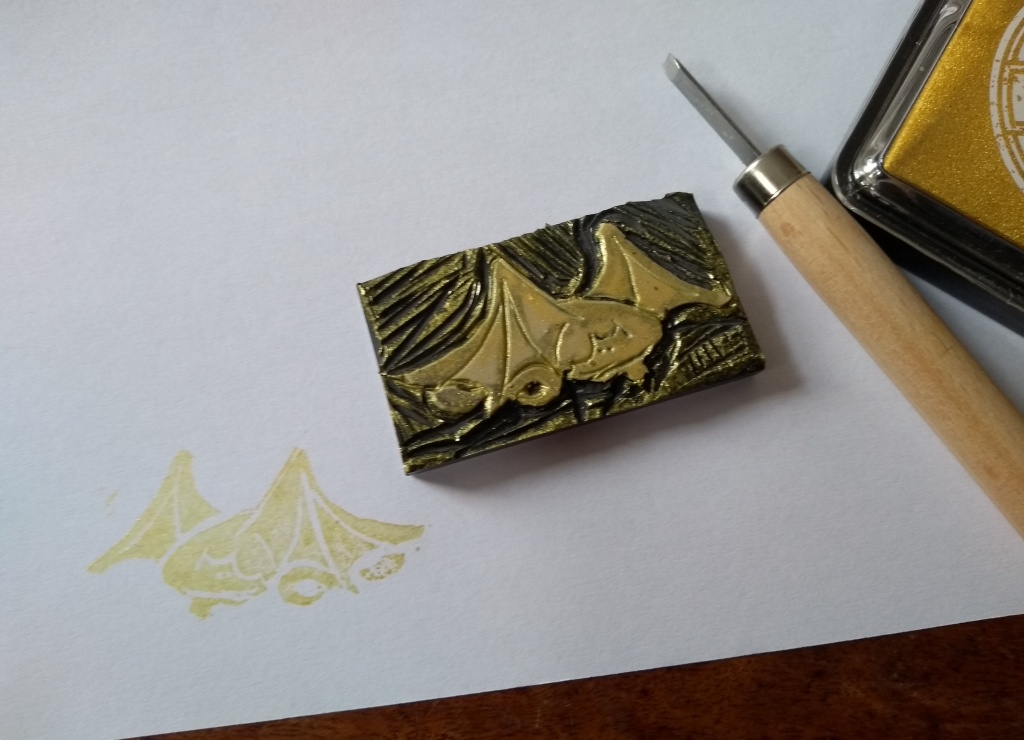 A linocut of a sleeping dragon curled up, with a cutting tool to the right and a print of the linocut in gold ink on white paper